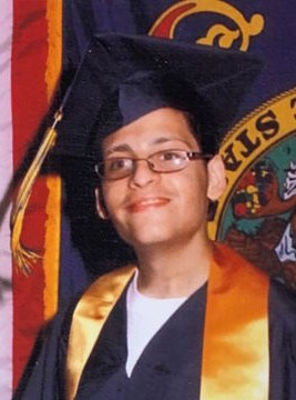 Photo of Moses Rodriguez, a young man with tan skin and black hair, wearing a graduation mortarboard and robe with a yellow sash. He is wearing glasses and smiling awkwardly for the camera.