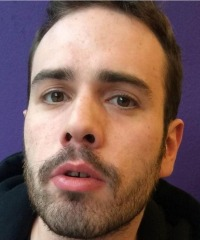 Photo of Christopher Laskaris, a young man with dark hair and light skin; he has a neatly trimmed beard and mustache.
