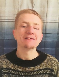 Photo of Carl DeBrodie, a young man wearing a brown sweater. He has pale skin, blond hair, and a goatee. He is smiling, showing a gap in his front teeth.