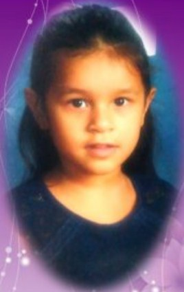 Photo of Brianna Saenz. She is a young girl with long black hair, brown eyes, and tan skin. She is wearing a blue shirt. The photo is a portrait photo decorated with a purple flowered frame.
