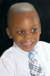 Photo of Marcus McGhee, an African-American child with a buzz cut. He is wearing a suit and a broad smile.