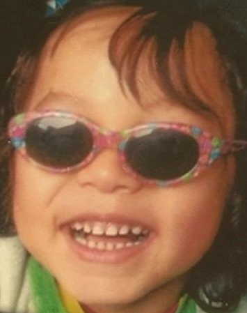 Photo of Tristan Neiland, a young child wearing pink flowered sunglasses. He has curly brown hair and fair skin.