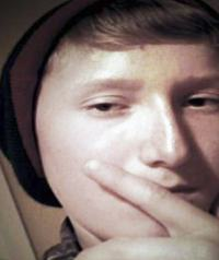 Photo of Gavin Mason. Close-up sepia-toned photo of a teenage boy with light skin and medium-brown hair, wearing a knit cap.