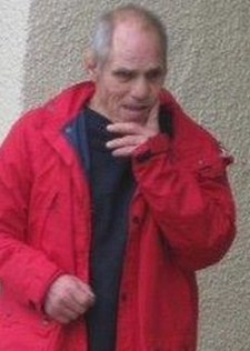 Photo of Anthony Dawson, an elder man wearing a bright red jacket over a black shirt. He has fair skin and is mostly bald except for a fringe of white hair. He has his hand to his face and looks somewhat puzzled.