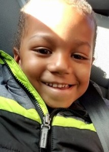Photo of Antonio di Stasio, a young boy with brown skin and very short brown hair. He is smiling at the camera, and wearing a black jacket with bright yellow stripes