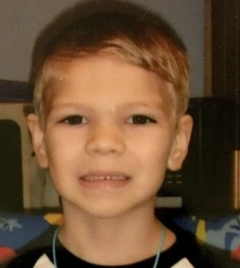 Photo of Dayvid Pakko, a young boy with fair skin, blond hair, and dark brown eyes. He is smiling for the camera.