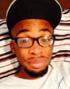 Photo of Rashard Pierce, a young man with brown skin and brown eyes, wearing a baseball cap and glasses. He has a thin mustache and beard.