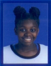 School photo of Shadaisja Hill, a teenage girl with dark-brown skin and a big smile. Her hair is done in two poofy buns atop her head.