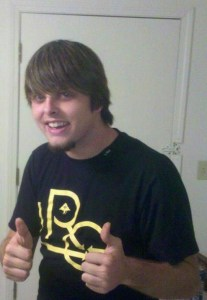 Matthew Lowry, a young man wearing a black T-shirt. He has shaggy brown hair and a trimmed beard. He is grinning at the camera and making a two-thumbs-up gesture.