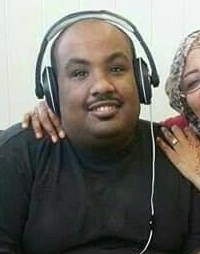 Photo of Samson Goitom. He has medium-brown skin and a mustache; his head is shaved and he is wearing noise-canceling headphones. At the right of the frame is a woman in a headscarf and glasses, with her arm around Samson.