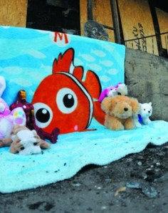 Memorial for Jeffery Bailey. A blanket with a cartoon clownfish is draped over some rubble at a fire scene; on the blanket are several plush toys and an action figure.
