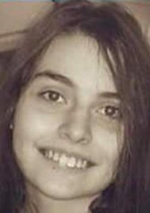 Sepia-tone photo of Kaylina Anderson, a teenage girl with light skin and dark, tangled hair, smiling for the camera.