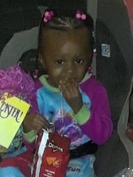 Photo of Tamira Billingslea, a toddler girl with dark-brown skin and black hair in braids decorated with pink beads. She is wearing a colorful sweater, and eating chips from a bag of Doritos.