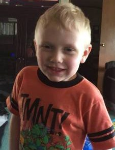 Photo of Joe Daniels, a young boy with blond hair and fair skin, wearing an orange Ninja Turtles T-shirt and smiling for the camera.