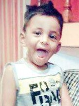 Photo of Samvith, a small boy with olive-toned skin and dark-brown hair, wearing a printed tank top. He has his mouth open and is looking at the camera happily.