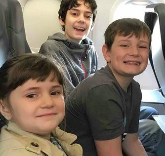 Photo of Tyler, Aidan, and Arianna Talmage. They are children with light-olive skin and brown hair, photographed sitting in a row of airplane seats and smiling for the camera.