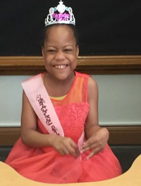 """Photo of Heaven Watkins, a small girl with brown skin and black hair pulled back under a silver crown. She is wearing a coral-colored dress and a sash that says """"Birthday Girl"""". Her face is scrunched up in a wide smile."""