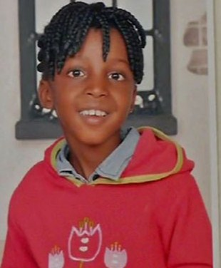 Photo of Katli Joja, a girl with brown skin and black hair in small, neat braids. She is wearing a red hoodie printed with flowers and smiling at the camera.