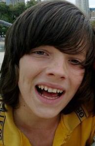 Photo of Josh Klumper, a teenage boy with chin-length brown hair and freckled skin, wearing a yellow polo shirt and smiling for the camera.