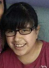 Photo of Mariah Lopez, a teenage girl with olive-toned skin and straight black hair in a ponytail and bangs, wearing glasses and a dark-red T-shirt; she is smiling for the camera.