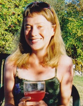 Photo of Colette McCulloch, a young blonde woman squinting in the sun, with her sunglasses propped up on her head. She is holding a wine glass full of red liquid and wearing a tank top.