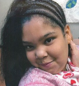Photo of Amaya Stethers, posing for a photo; she is a teenage girl with light-brown skin and hair in braids that curve around her head. She is wearing a pink and heart-print top.
