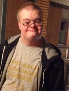 Photo of Eric Torell, a young man with Down syndrome; he has fair hair in a short buzz cut, and is wearing glasses and a jacket and T-shirt. He is smiling at the camera and his glasses are slipping down his nose.