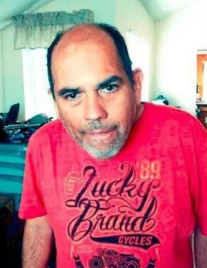 """Photo of a middle-aged balding man, with olive skin, dark hair, and salt-and-pepper beard; he is looking at the camera with a slight smile. He is wearing a red T-shirt that says """"Lucky Brand Cycles"""" in fancy script."""
