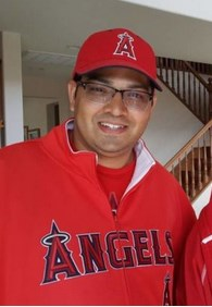 Photo of a Hispanic young man in glasses and red Angels baseball cap and sweater.