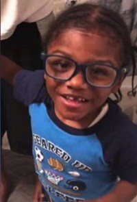 A small boy with thick glasses, front teeth missing, hair in cornrows, wearing a soccer shirt.