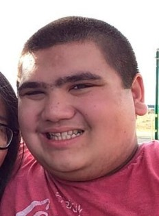 Photo of Eric Parsa, a chubby teenage boy with light skin and dark hair in a buzz cut. He is smiling awkwardly for the camera. His T-shirt is red. He is leaning against a woman off to the left of the frame.