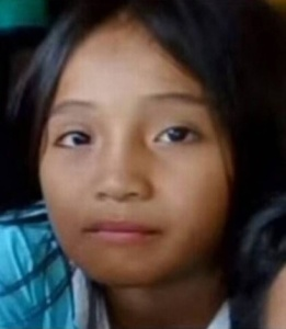 Photo of young Filipino girl, looking at the camera with a solemn expression.