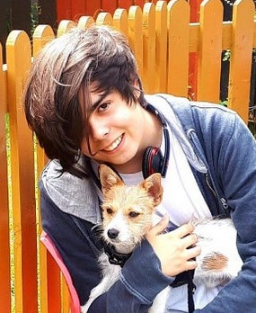 Photo of teenage boy with fair skin and brown hair hanging over his face. He has headpones around his neck. He is holding a small terrier and smiling for the camera.
