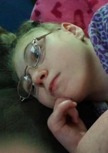 Photo of a teenage girl with blond hair and glasses, lying down.