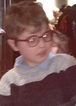 Blurry photo of a young boy wearing a sweater and thick glasses. His dirty-blond hair is parted on the side and his expression is neutral.