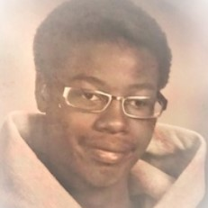 Portrait photo of a young black man with glasses.