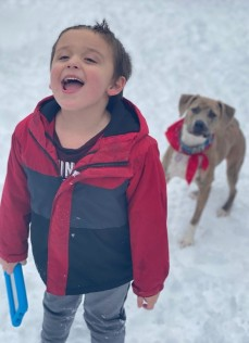 Photo of a small boy standing in the snow, holding the leash to a brown dog.