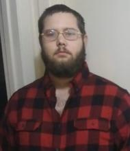Photo of a man with brown hair, fair skin, and a full beard. He is wearing glasses and a plaid flannel shirt.