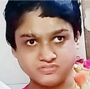 Photo of a young Indian woman, her dark hair cut short, a small scar across her eyebrow and one eye turned slightly outward, looking at the camera with a thoughtful expression.